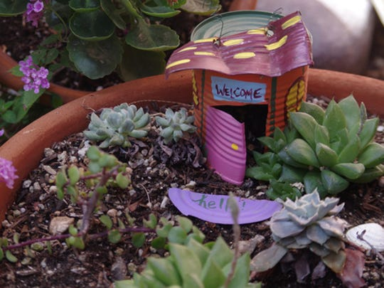 "This undated photo provided by Victoria Hannley shows a fairy garden made by Hannley, in Tuscon, Ariz. Hannley writes the DIY blog ""Dazzled While Frazzled"" and created the fairy garden with objects left over from her daughter's birthday party and an empty tin soup can."