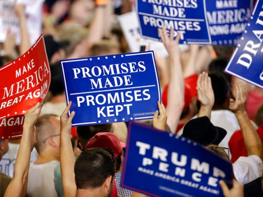 Supporters hold up signs as President Donald Trump speaks at a rally in Harrisburg, Pa., April 29.