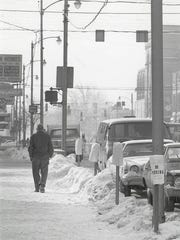 A man walks in downtown Marion as snow began to fall