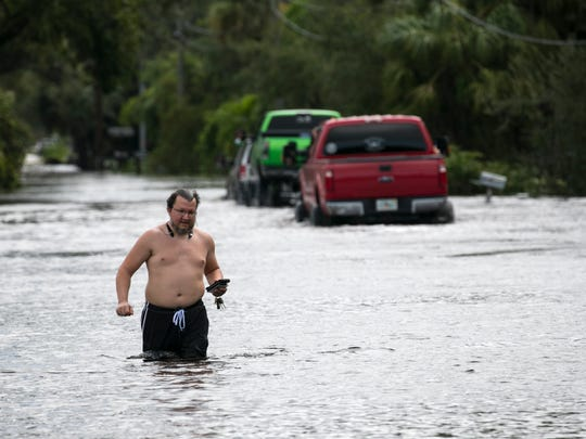 Sean Roper walks through flood waters on Cemetery Road in Buckingham on Monday following Hurricane Irma.