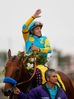 Victor Espinoza waves to the cheering crowd after winning the Breeders' Classic on American Pharoah.  
