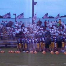 Players and fans stand together at a high school football game to share a moment of silence for the seven victims of a murder Thursday.