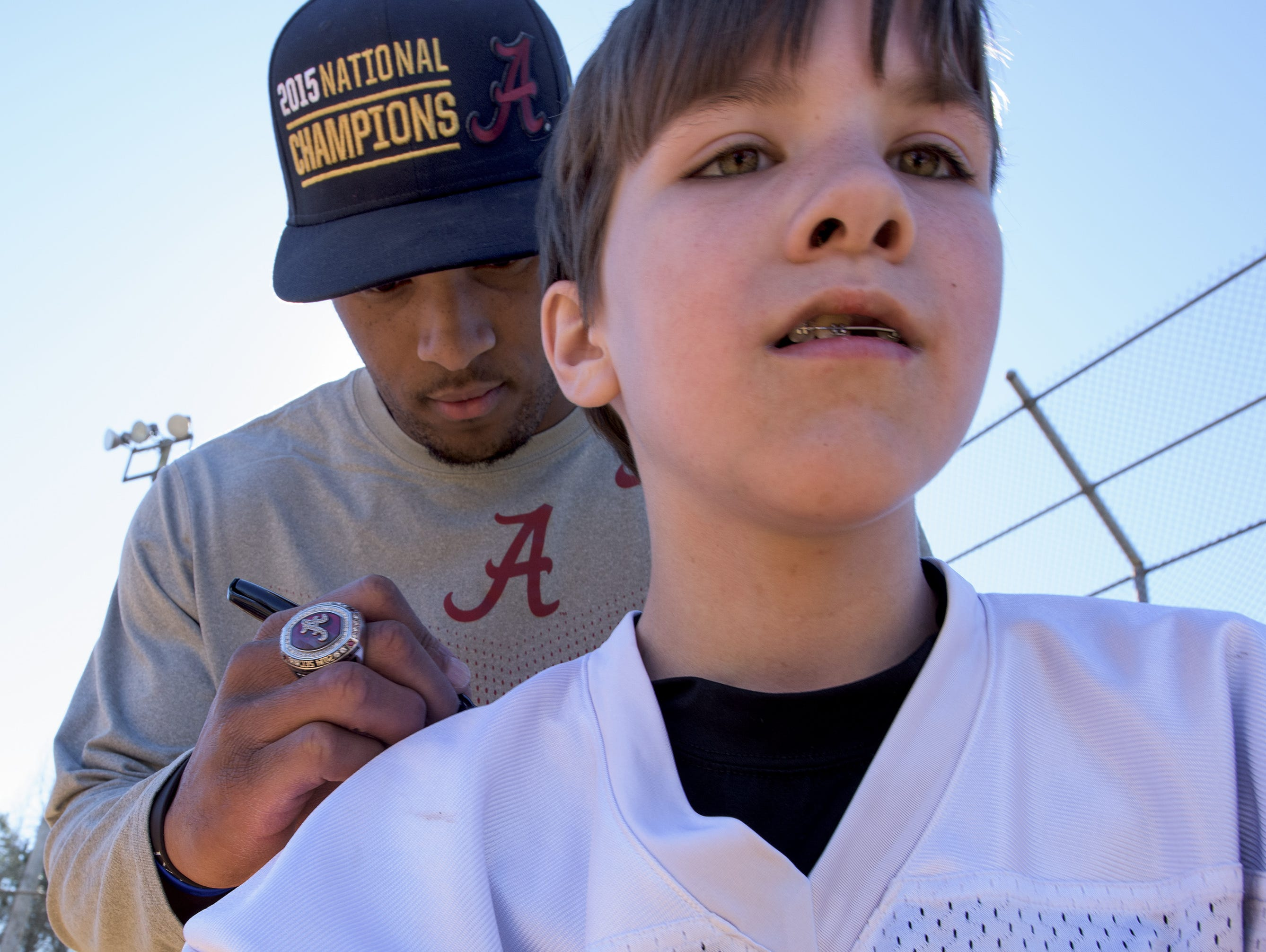 CFB National Championship Game MVP O.J. Howard signs an Autauga Academy jersey for Aaron Powell as the town of Autaugaville, Ala. holds a parade in honor of Howard on Saturday February 27, 2016.