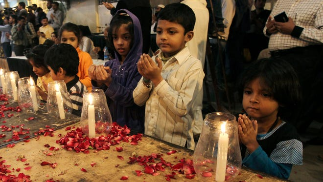 Pakistani children chant prayers during a candlelight vigil for the victims of a Taliban attack on a school in Peshawar, Pakistan, on Tuesday. Taliban gunmen stormed a military-run school in the northwestern Pakistani city, killing more than 140, officials said, in the highest-profile militant attack to hit the troubled region in months.
