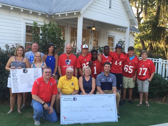 Pike Road Patriot Fund Committee members hold a thank you note from Pike Road School  football players. PRS Superintendent Dr. Suzanne Freeman, PRS Board of Education members and PRS football coach Patrick Browning hold a $5,000 check presented to the PRS football team.