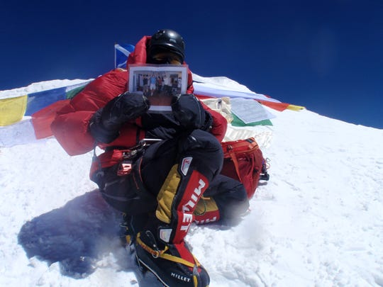 Jen Loeb at the summit of Mount Everest in May 2016, holding a photo of her friends.