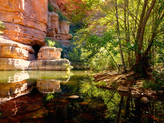 Parsons Trail leads through lush foliage along red rock cliffs at the water's edge.
