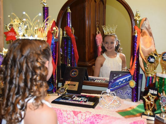 Olivia Avery, 11, surrounded by awards from beauty pageants and dancing in her Binghamton home earlier in October