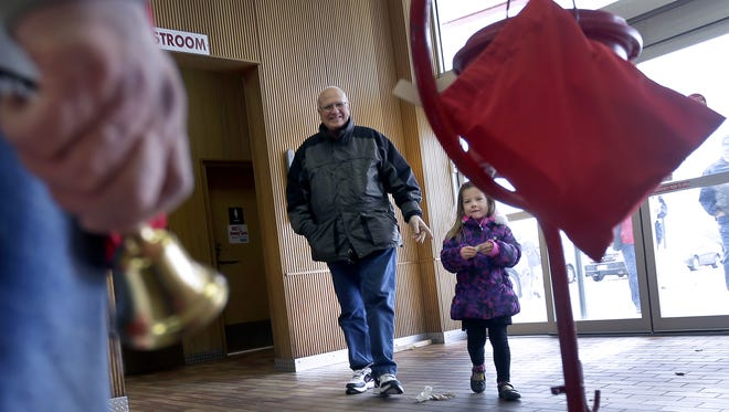 Al Schroeder and Finley Paul make a donation as volunteers ring bells Friday at Woodman's Food Market in Grand Chute. It was the first day of the 2015 Salvation Army Red Kettle Campaign.