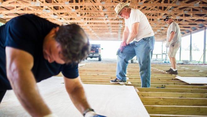 Matthew Gillum, left, Duane Jenkins, center, and Ray Turner work on the new Blue Jar Barn on Thursday in Anderson.
