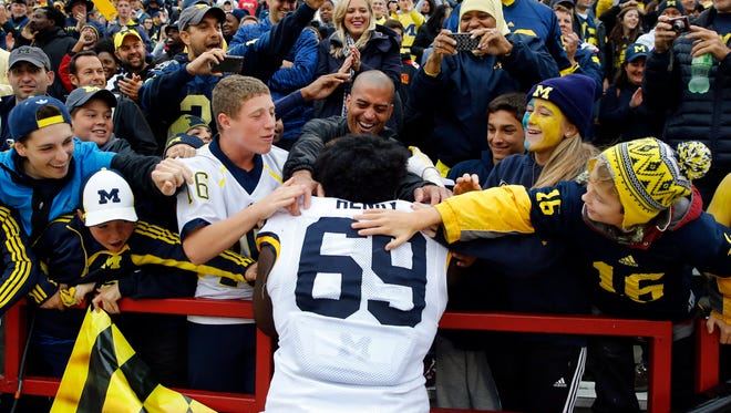Fans celebrate with Michigan defensive tackle Willie Henry (69) after a game against Maryland on Saturday, Oct. 3, 2015, in College Park, Md.
