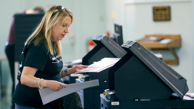 Kim Catalanello votes at Perinton Community Church in Fairport where polls opened at 6 a.m. Tuesday.