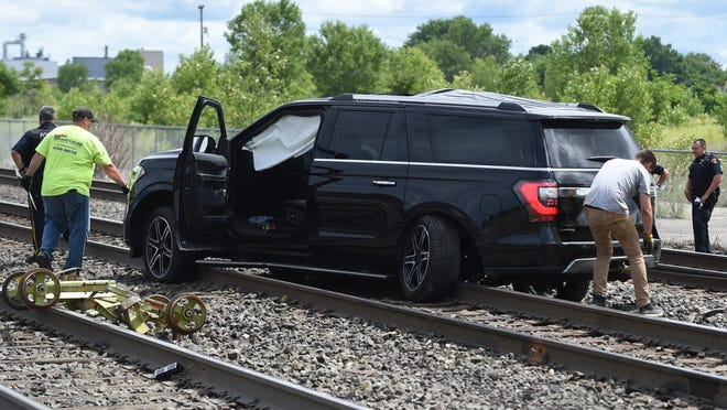 A Ford Expedition is towed from the railroad tracks at West 14th and Raspberry streets on Monday after colliding with a CSX Railroad tamping machine that was performing maintenance on the tracks.