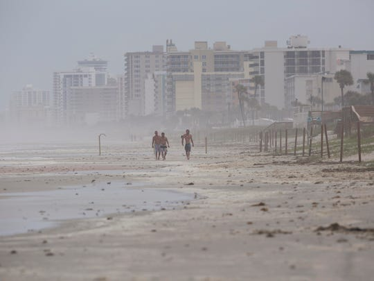 Oct 6, 2016; Daytona Beach, FL, USA; Surfers make their way up Daytona Beach prior to Hurricane Matthew. Mandatory Credit: Andrew West/The News-Press via USA TODAY NETWORK