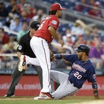 The Minnesota Twins' Eddie Rosario (20) slides into third safely on a single by Byung Ho Park, next to Washington Nationals third baseman Anthony Rendon (6) during the fourth inning Friday in Washington. The Nationals won 4-3.