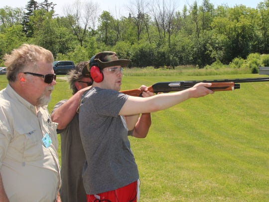 Robert Collett of Sussex (with black cap) gets assistance from his father, Robert Collett of Milwaukee (center), and Jeff Marusic during Take Aim at Cancer at Schultz Resort Rod & Gun Club in Muskego. Robert Collett, who is blind, has been treated for Hodgkin lymphoma.