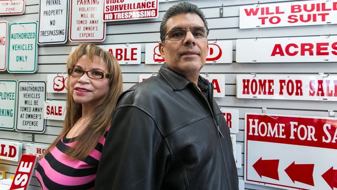 Signergy owners Diana and Marvin Herrera are pictured near a wall of signs in the store on Wednesday, located at 1695 N. Main Street.