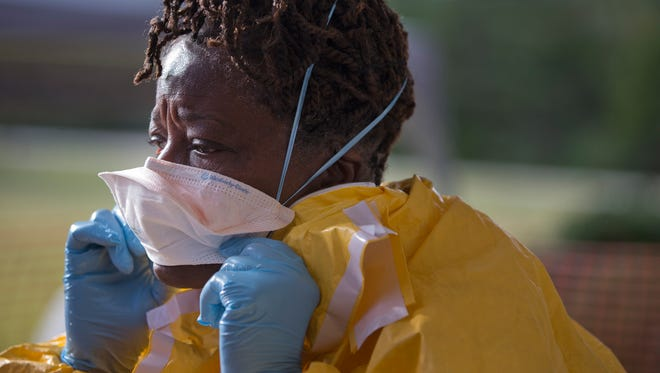 Licensed clinician Roseda Marshall, of Liberia, disrobes after a simulated training session on  Oct. 6 in Anniston, Ala.