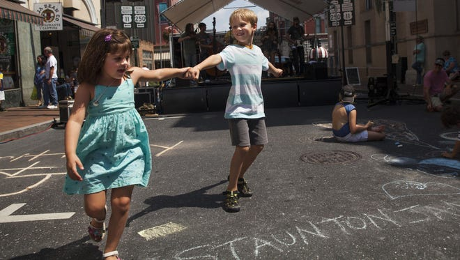 Declan White, center, dances with his cousin, Eleanor Troxell, during the Staunton Jams in Aug. 2014.