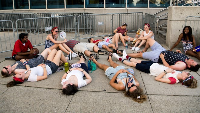 People rest in the shade of Bridgestone Arena on Wednesday during the 'Let Freedom Sing!' festivities.
