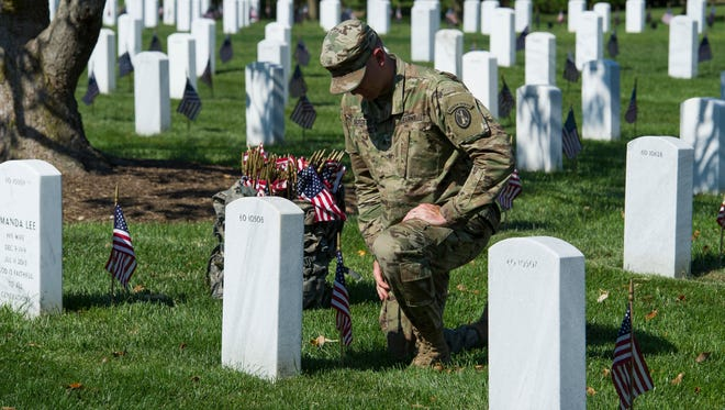 A member of the Army 3d U.S. Infantry Regiment, The Old Guard, pauses to honor a fallen soldier while places flags a the gravesite of the nation's fallen military heroes during its annual Flags In ceremony at Arlington National Cemetery, ahead of Memorial Day.