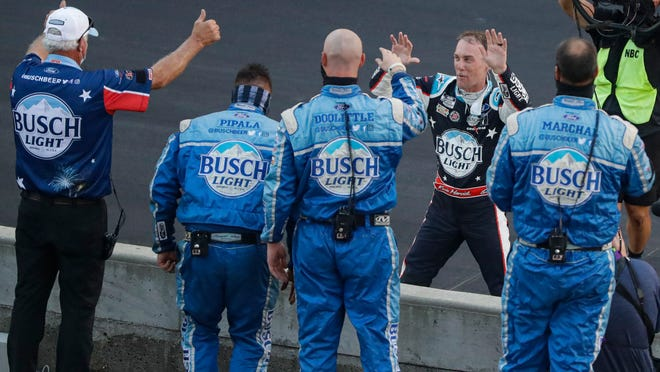 Kevin Harvick, on far side of wall, celebrates with his crew after winning the NASCAR Cup Series auto race at Indianapolis Motor Speedway in Indianapolis, Sunday, July 5, 2020.