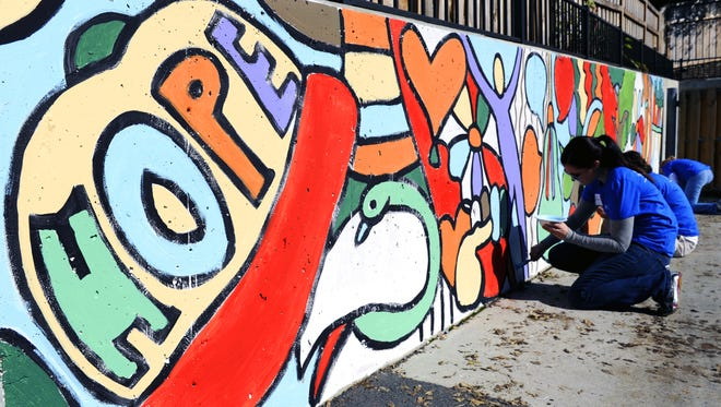 Amanda Stencel of HCA volunteers painting a large mural on the playground at Safe Haven Family Shelter on Thursday Oct. 23, 2014. The art project/mural was designed by artist Andee Rudloff.