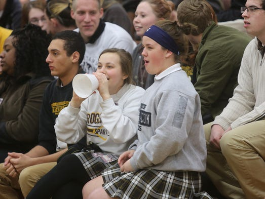 Seniors Grace Cunningham, left, and Megan Mitsch cheer during a pep rally to send the Roger Bacon boys' basketball team off to the state Final Four championship.