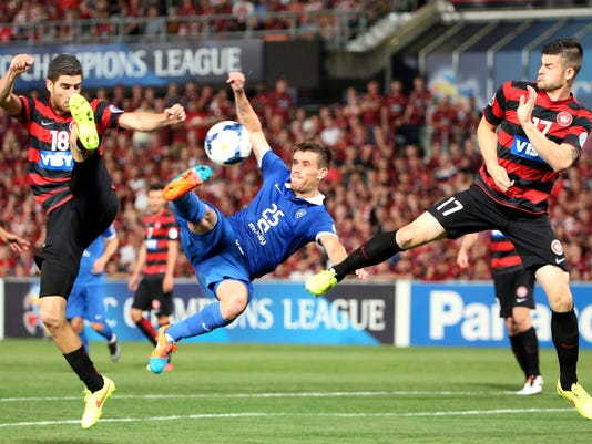 Saudi Arabia's Al Hilal's Mihai Doru Pintilii, center, tries to shoot as Western Sydney Wanderers' Brendan Hamill, right, and Lacopo La Rocca defend it during their Asian Champions League Final soccer match in Sydney, Australia, Saturday, Oct. 25, 2014. The Wonderers won the match 1-0. (AP Photo/Rob Griffith)