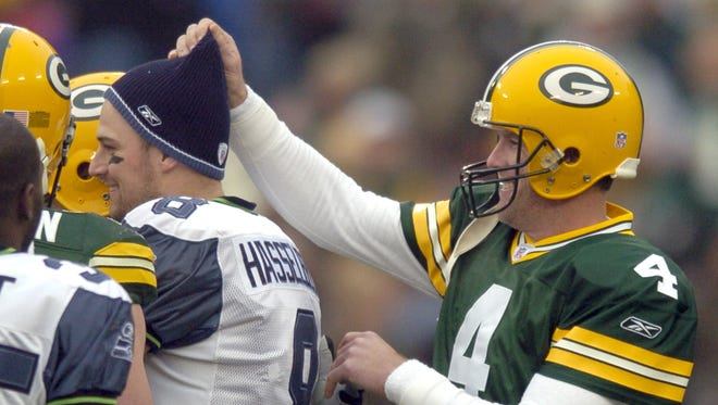 Packers quarterback Brett Favre has some fun with Seattle Seahawks quarterback Matt Hasselbeck's hat before the start of their Jan. 1, 2006, game at Lambeau Field. Hasselbeck served as Favre's backup with the Packers in 1999 and 2000.