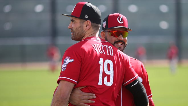 Cincinnati Reds first baseman Joey Votto (19) and Cincinnati Reds third baseman Eugenio Suarez (7) embrace on the first day of full-squad workouts, Monday, Feb. 19, 2018, at the Cincinnati Reds Spring Training facility in Goodyear, Arizona.