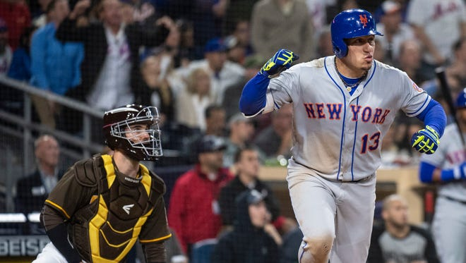 New York Mets' Asdrubal Cabrera, right, watches his three-run home run in front of San Diego Padres catcher Austin Hedges during the seventh inning of a baseball game in San Diego, Friday, April, 27, 2018.