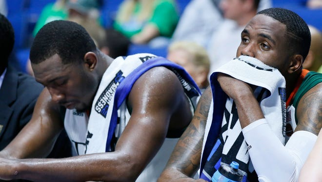 Miami's Ja'Quan Newton, right, and Davon Reed, left, sit on the bench late in the second half of a first-round game against Michigan State in the men's NCAA college basketball tournament in Tulsa, Okla., Friday, March 17, 2017. Michigan State won 78-58. (AP Photo/Sue Ogrocki)