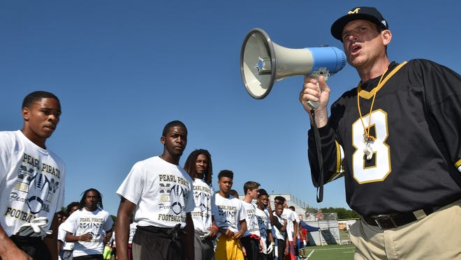 Michigan football coach Jim Harbaugh encourages more than 500 high school football players in a speed drill at a satellite camp June 8, 2016, in Pearl, Miss.