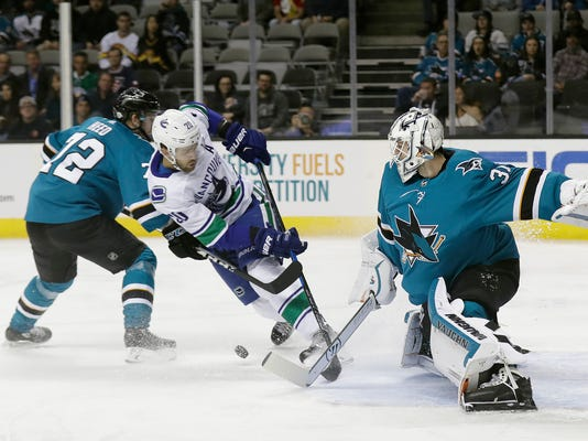San Jose Sharks goaltender Martin Jones, right, stops a shot from Vancouver Canucks center Brandon Sutter, center, during the first period of an NHL hockey game Thursday, Feb. 15, 2018, in San Jose, Calif. (AP Photo/Marcio Jose Sanchez)