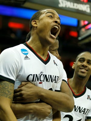 Bearcats guard Troy Caupain (10) is hugged by forward Jermaine Sanders after tying the game at the end of regulation on Thursday in Louisville.