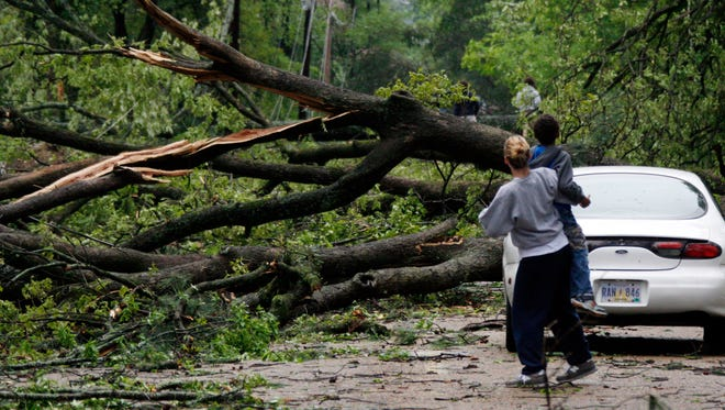 As dusk falls in northeast Jackson, Miss., Anna Marie Payne holds her 7-year-old son Bronson Payne up so he can get a better view of the blocked street following Friday afternoon's powerful storms and possible tornadoes that hit the state, April 4, 2008.