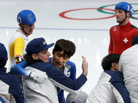 Korea's coach Bob de Jong of The Netherlands, hugs gold medalist Lee Seung-hoon of South Korea as silver medalist Bart Swings of Belgium, left, and Livio Wenger of Switzerland, right, stand by after the men's mass start speedskating race at the Gangneung Oval at the 2018 Winter Olympics in Gangneung, South Korea, Saturday, Feb. 24, 2018. (AP Photo/John Locher)