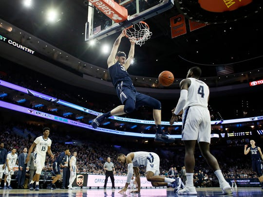 Xavier's Zach Hankins (35) hangs from the rim after a dunk during the first half of the team's NCAA college basketball game against Villanova, Friday, Jan. 18, 2019, in Philadelphia. (AP Photo/Matt Slocum)