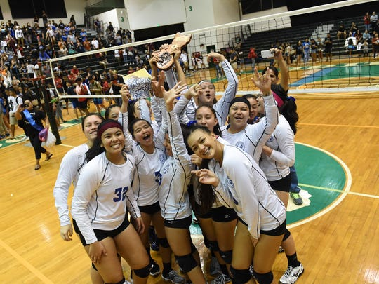 The Notre Dame Lady Royals celebrate after defeating the St. John's Knights for the Independent Interscholastic Athletic Association of Guam Girls Volleyball Championship at the University of Guam Calvo Field House on Oct. 20, 2017.