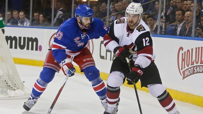 The New York Rangers' Keith Yandle (left) defends the Arizona Coyotes' Brad Richardson (12) during the first period of an NHL hockey game Thursday, Oct. 22, 2015, in New York.