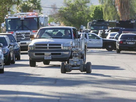 A robot leads two vehicles away from the scene of an