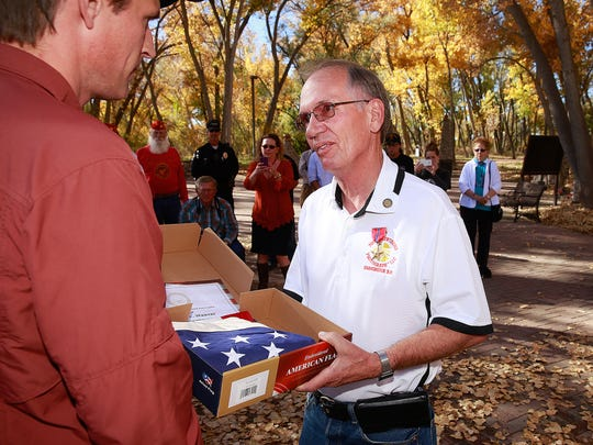 U.S. Marine Corps Lance Cpl. Thomas Weaver, right, receives an American flag and a Bronze Star from U.S. Sen. Martin Heinrich on Thursday at All Veterans Memorial Plaza at Berg Park in Farmington.