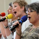 Donna Laughlin, right, sings with friend Rhonda Black, center, and niece Cathy Hutto at Wednesday's concert.