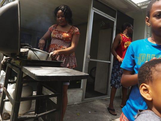 Fort Myers resident Clemene Cherilus cooks a meal of