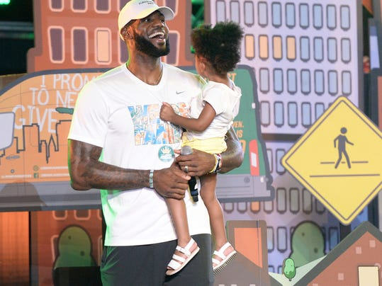 Cleveland Cavaliers' LeBron James laughs as he leaves the stage holding his daughter, Zhuri, during the We Are Family Reunion at Cedar Point in Sandusky, Ohio, Tuesday, Aug. 15, 2017. (Erin McLaughlin/The Sandusky Register via AP)