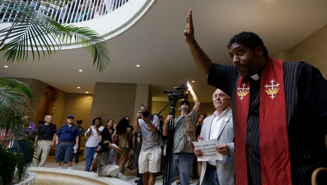 """The Rev. William Barber, right, addresses an NAACP-led """"Moral Monday"""" demonstration last month at the legislature in Raleigh, N.C."""
