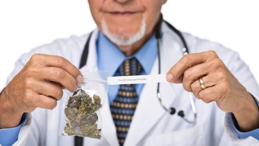 Part of senior doctor holding cannabis