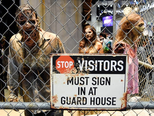 """Zombie characters walk inside a cage at the """"Walking"""