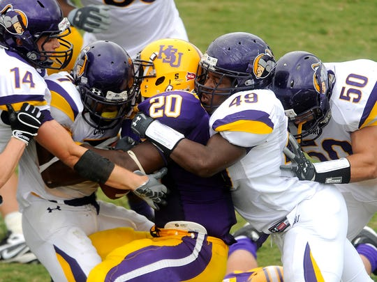 Hardin-Simmons running back Steven Rockwell (20) gets sandwiched between Mary Hardin-Baylor defenders Brett Parker (14), Bryson Tucker (7), Jerrad Jefferson (49) and Brenson Shaw during the third quarter of UMHB's 23-7 win Saturday, Oct. 3, 2009, at Shelton Stadium in Abilene.